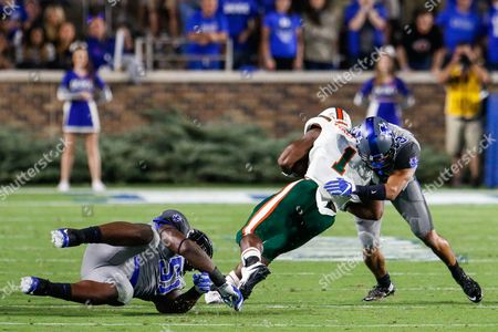 Jordan Hayes (13) of the Duke Blue Devils stops Mark Walton (1) of the Miami Hurricanes in the NCAA matchup between Miami and Duke at Wallace Wade Stadium in Durham, NC