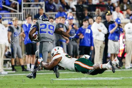 Darrion Owens (58) of the Miami Hurricanes wraps up the legs of Shaun Wilson (29) of the Duke Blue Devils in the NCAA matchup between Miami and Duke at Wallace Wade Stadium in Durham, NC