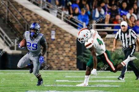 Shaun Wilson (29) of the Duke Blue Devils gets away from Jaquan Johnson (4) of the Miami Hurricanes in the NCAA matchup between Miami and Duke at Wallace Wade Stadium in Durham, NC