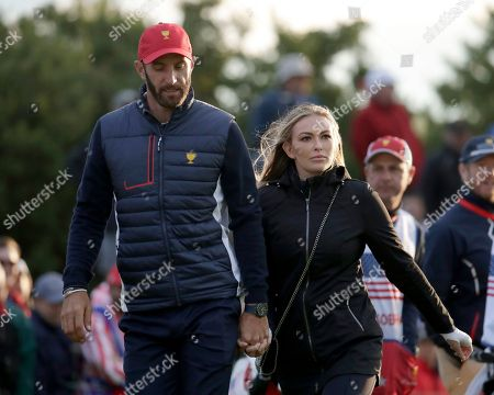 Dustin Johnson, Paulina Gretzky. United States team member Dustin Johnson and his wife Paulina Gretzky walk toward the 18th hole to watch play during the four-ball golf matches on the third day of the Presidents Cup at Liberty National Golf Club in Jersey City, N.J