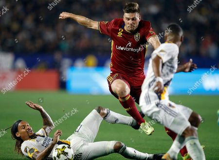 Stock Photo of David Horst, Jermaine Jones. Real Salt Lake defender David Horst, center, leaps over the tackle by Los Angeles Galaxy midfielder Jermaine Jones (13) to get to the ball during the second half of an MLS soccer game in Carson, Calif