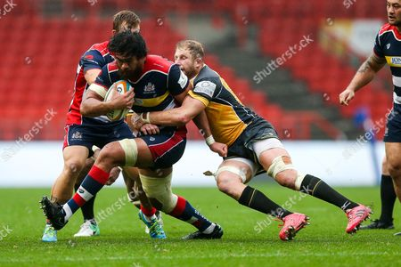 Steven Luatua of Bristol Rugby is tackled by Mark Bright of Ealing Trailfinders