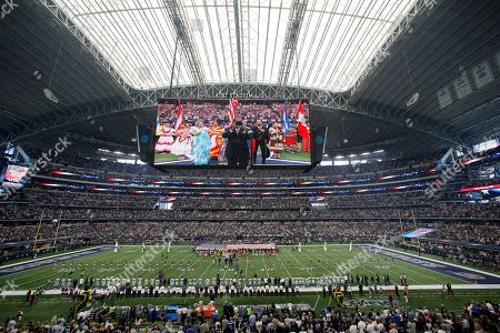 Entertainer Freddie Jones is shown on the large video screen playing the national anthem, joined by fans, teams and folkloric dancers in this general, overall, view, of AT&T Stadium before an NFL football game between the Los Angeles Rams and Dallas Cowboys, in Arlington, Texas. The League is celebrating Hispanic Heritage Month