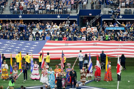 Entertainer Freddie Jones, bottom center, plays the national anthem as folklorico dancers and the Los Angeles Rams participate before an NFL football game against the Dallas Cowboys, in Arlington, Texas. The league is celebrating Hispanic Heritage Month