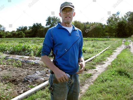 Andy Jones of the Intervale Community Farm stands near a sweet potato crop at the farm in Burlington, Vt. The farm is irrigating crops more frequently due to longer spans of dry weather
