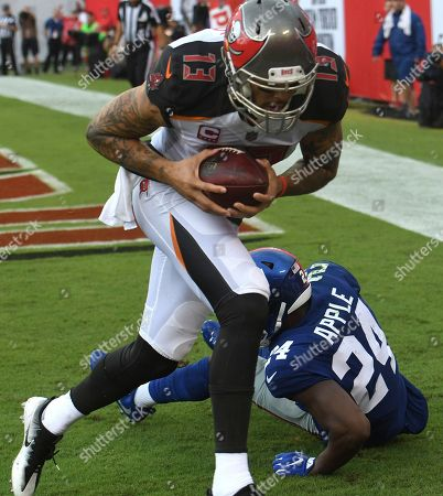Mike Evans, Eli Apple. Tampa Bay Buccaneers wide receiver Mike Evans (13) pulls in a 6-yard touchdown reception in front of New York Giants cornerback Eli Apple (24) during the first quarter of an NFL football game, in Tampa, Fla