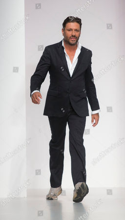 Designer Filippo Scuffi of Daks walks on the runway as spectators applaud after his show during London Fashion Week Spring/Summer 2014, at Somerset House in central London