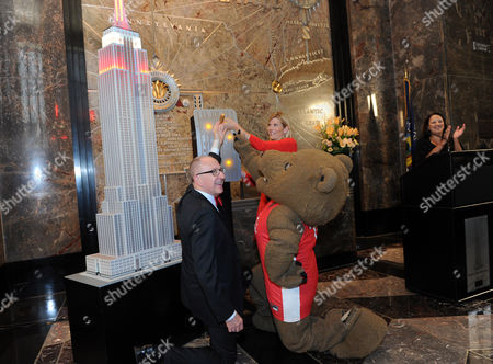 Cornell University President David Skorton, left, Kate Snow, NBC News national correspondent and Cornell alumna, and the Big Red Bear flip the switch to light up the Empire State Building red and white to kick-off Cornell University's 150th anniversary celebration year, in New York