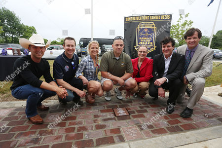 """From left, Country music singer Justin Moore, NASCAR driver Kurt Busch, Armed Forces Foundation President and Executive Director Patricia Driscoll, Crown Royal Brand Director Abby Wise, Big Machine Label Group Founder and CEO Scott Borchetta and Indianapolis Motor Speedway COO Doug Boles pose with Retired Gunnery Sergeant Samuel Deeds, center, winner of Crown Royal's """"Your Hero's Name Here"""" program, behind the replica Yard of Bricks in Erlanger, Ky. on . As winner, Deeds will receive naming rights to the NASCAR Sprint Cup Series Race at Indianapolis Motor Speedway on July 28, 2013"""