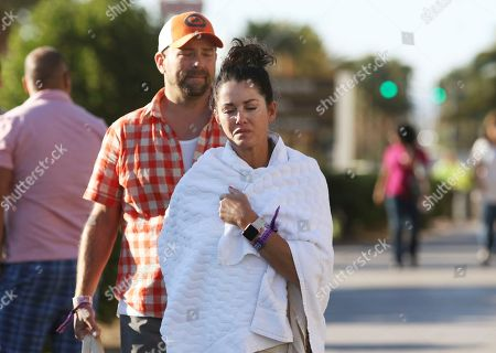 Melissah Burke, Stephen Burke. Melissah Burke and her husband Stephen, of Seattle, walk along the Las Vegas Strip near Mandalay Bay hotel and casino, in Las Vegas. The couple, who were attending the music festival last night where a mass shooting occurred, found refuge in a nearby apartment and casino
