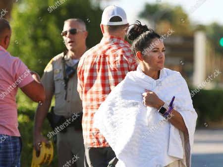 Melissah Burke, Stephen Burke. Melissah Burke looks off while her husband Stephen, behind her, speaks with cops on the Las Vegas Strip near Mandalay Bay hotel and casino, in Las Vegas. The couple, who were attending the music festival last night where a mass shooting occurred, found refuge in a nearby apartment and casino