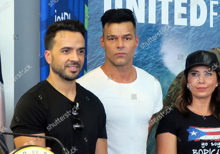 Puerto Rican singers Luis Fonsi (L) and Ricky Martin (C), accompained by well-being and of the health activist , Laura Posada (R), attend a press conference at the Luis Munoz Marin International airport in San Juan, Puerto Rico, 02 October 2017.   Ricky Martin, Luis Fonsi, Chayanne, Gloria Estefan and Nicky Jam, among other artists, arrived in Puerto Rico to join forces and deliver supplies to victims of hurricane Maria.