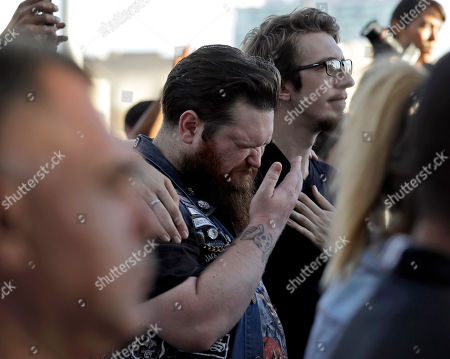 Sean Bolger is comforted by a friend during a vigil at City Hall in Las Vegas, . The vigil was held in honor of the over 50 people killed and hundreds injured in a mass shooting at an outdoor music concert late Sunday