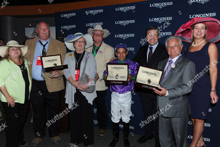 Jennifer Judkins, right, and Juan-Carlos Capelli, third right, both of Longines, award trainer Art Sherman, second right, jockey Victor Espinoza and owners Steve and Carolyn Coburn, second left, and Perry and Denise Martin, left, with their Longines Conquest Classic chronographs after California Chrome won the 140th Kentucky Derby, in Louisville, Ky. Longines, the Swiss watchmaker known for its famous timepieces, is the Official Watch and Timekeeper of the 139th annual Kentucky Derby