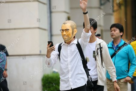 A Shopper wearing a Steve Jobs mask enters the Apple Store in Tokyo's Omotesando shopping district in Japan. Apple Inc.'s new iPhone 8 and iPhone 8 Plus smartphones went on sale in Japan.