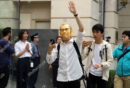 The first customer wearing a mask of Steve Jobs enters an Apple store to purchase Apple's iPhone 8 in Tokyo