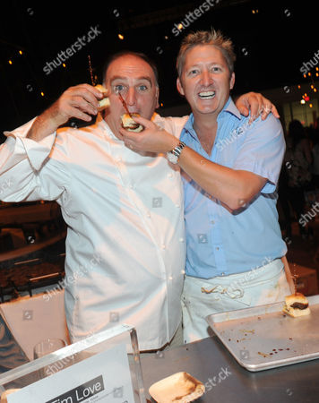 IMAGE DISTRIBUTED FOR TRAVEL + LEISURE - Chef Tim Love, right, feeds Chef Jose Andres one of his signature burgers at the 2012 Travel + Leisure Global Bazaar at the Lexington Armory in New York, . The three-day bazaar features food, performances and shopping from around the world
