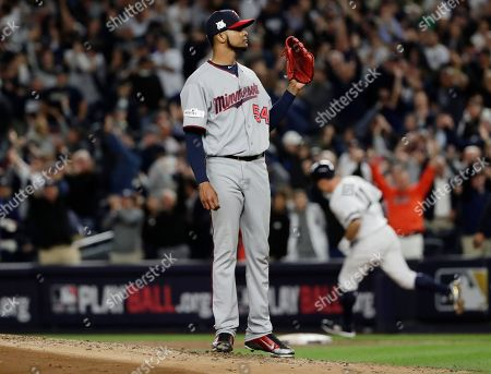 Minnesota Twins starting pitcher Ervin Santana waits as New York Yankees' Brett Gardner (11) runs the bases after hitting a home run during the second inning of the American League wild-card baseball game, in New York