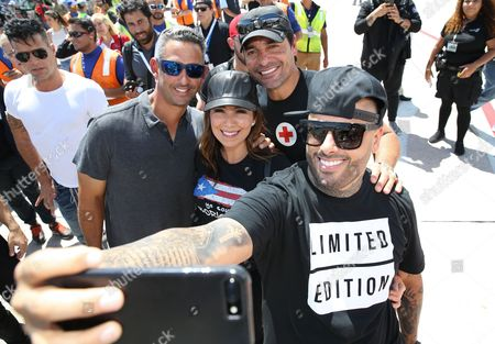 Singer Nicky Jam poses with former professional baseball player Jorge Posada, his wife, Laura Posada, and singer Chayanne at Luis Munoz Marin International Airport in San Juan The mission was part of a #100x35JetBlue special relief effort aimed at raising awareness and delivering aid to the people of Puerto Rico.