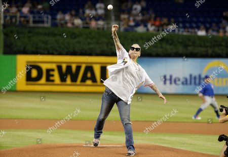 Actress Lori Petty throws a ceremonial pitch before a baseball game between the Miami Marlins and Chicago Cubs, in Miami. Petty was in the 1992 film A League of Their Own