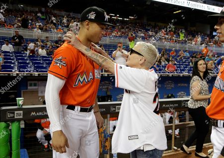Stock Image of Lori Petty, Giancarlo Stanton. Actress Lori Petty, right, hugs Miami Marlins right fielder Giancarlo Stanton before a baseball game between the Miami Marlins and Chicago Cubs, in Miami. Petty was in the 1992 film A League of Their Own