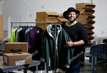 """Co-owner Daniel Franzese poses for a photo at """"The Winston Box"""" in showroom in Gardena, Calif. The Winston Box is a monthly subscription box that designs and makes its own clothes for big guys. More online retailers are chasing after plus-sized men, selling big sizes of slim-cut jeans, faux leather jackets and other trendy clothing that can be hard to find at the local big and tall store"""