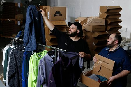 """Daniel Franzese, Wil Cuadros. Co-owners Daniel Franzese, left, and Wil Cuadros select clothes for """"The Winston Box"""" at their showroom in Gardena, Calif. The Winston Box is a monthly subscription box that designs and makes its own clothes for big guys. More online retailers are chasing after plus-sized men, selling big sizes of slim-cut jeans, faux leather jackets and other trendy clothing that can be hard to find at the local big and tall store"""