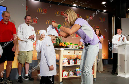Time Olympic medalist Dara Torres, right, presents a participation medal to Gabriel Bellintani Dassi, 8, of Brazil after the McDonald's Champions of Food Challenge at the McDonald's flagship restaurant on the Olympic Park, in London, England. The cooking contest was created to encourage children to eat more fruits and vegetables and inspire McDonald's menu innovation