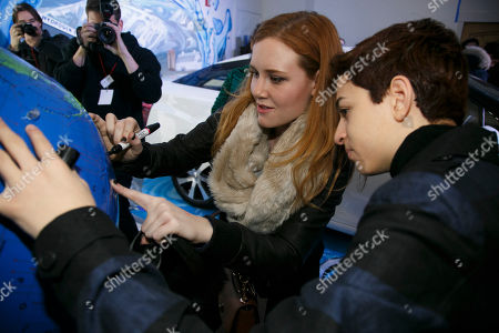 Josie Totah and Madisen Beaty, from right, sign their names to an inflatable globe for the Earth Day Network at the Toyota Mirai Music Lodge as part of the Sundance Film Festival, in Park City, Utah