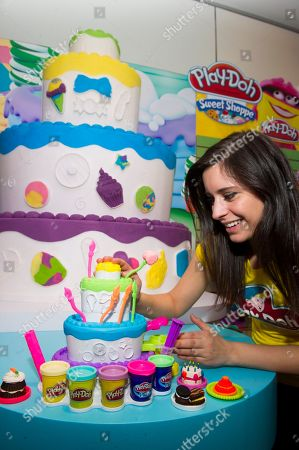 Demonstrator Emily Drooby stacks up layers of fun with the CAKE MOUNTAIN playset at the Hasbro showroom during the American International Toy Fair on in New York. With multiple cake half molds, three layers, and fluffy PLAY-DOH PLUS compound, there are tons of ways to make amazing PLAY-DOH cake creations