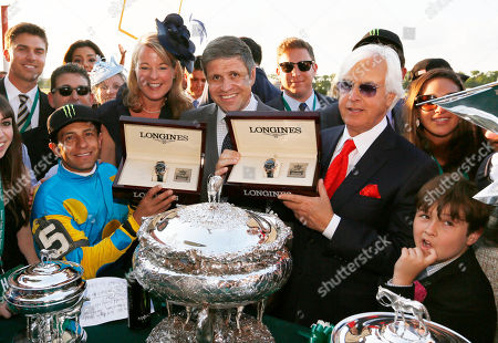 Jennifer Judkins and Juan Carlos Capelli, center, both of Longines, award Jockey Victor Espinoza, left, and Bob Baffert, right, Longines Conquest Classic 18K gold timepieces after Espinoza rode American Pharaoh to win the first Triple Crown in 37 years at the 147th Belmont Stakes at Belmont Park Race Track, in Elmont, N.Y