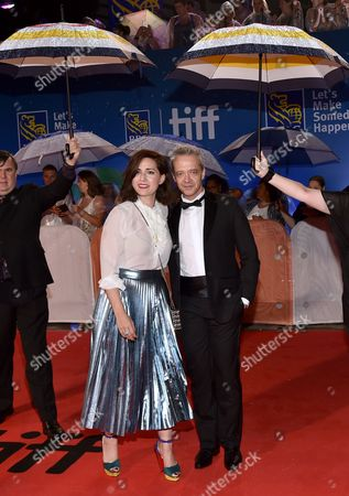 Rebecca Zlotowski, left, and Emmanuel Salinger arrive at the Planetarium premiere while event staff hold umbrellas to protect from the rain on day 3 of the Toronto International Film Festival at Roy Thomson Hall, in Toronto