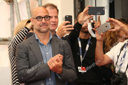 Stanley Tucci and Thomas McCarthy watch as Mark Ruffalo poses for photographers at the photo call for the film Spotlight during the 72nd edition of the Venice Film Festival in Venice, Italy, . The 72nd edition of the festival runs until Sept. 12