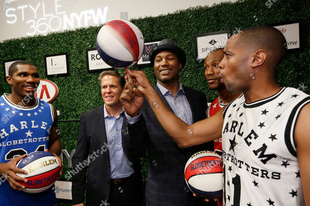Harlem Globetrotters, from left, Thunder Law, CEO Kurt Schneider, Smooth Staples and Cheese Chisholm spin the ball with former World Heavyweight Champion Lennox Lewis, center, on the red-carpet at the Harlem Globetrotters/Angela Simmons show during New York Fashion Week, New York, N.Y
