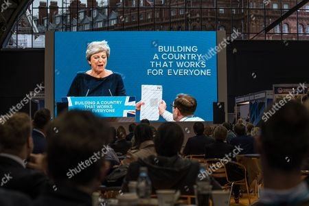 Watched by delegates on a big screen in the conference exhibition, stunt comedian Simon Brodkin (aka Lee Nelson) hands Prime Minister Theresa May a P45 form during her keynote speech on the fourth and final day of the Conservative Party Conference