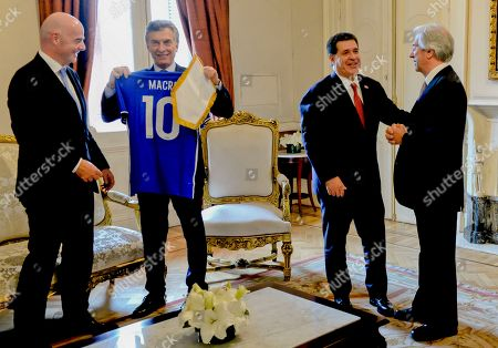 In this photo provided by the Argentine Presidency, Argentina's President Mauricio Macri, second left, looks at a soccer jersey with his name, next to FIFA President Gianni Infantino, left, as Paraguay's President Horacio Cartes, second right, talks to Uruguay's President Tavare Vazquez, right, at Casa Rosada in Buenos Aires, Argentina, . The three South American countries say they will chase a bid for the 2030 World Cup, which is expected to be competitive with China and Britain possibly in the mix