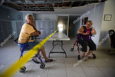 Stock Picture of Manuela Libran, 67, left, and Maria Roman, residents of the Aires de Manantial, a residence for low-income elderly people, sit by caution tape placed there to keep people away because the ceiling needs repair, in Trujillo Alto, Puerto Rico, . Residents say the building administration ordered them to leave ahead of the Hurricane Maria. Now lights are back on and food has started arriving