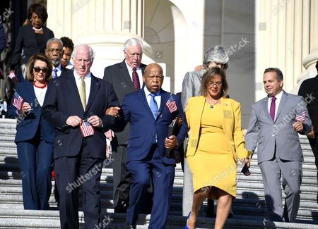 United States Representative John Lewis (Democrat of Georgia), center, and US Representative Mike 'Sugar Bear' Thompson (Democrat of California), left, and US Representative Robin Kelly (Democrat of Illinois) lead US House Democrats down the East Steps of the US Capitol to make a statement against gun violence in the wake of the Las Vegas Massacre in Washington, DC.