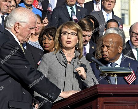 Stock Picture of Former United States Representative Gabrielle Giffords (Democrat of Arizona) makes remarks as US House Democrats appear on the East Steps of the US Capitol to make a statement against gun violence in the wake of the Las Vegas Massacre in Washington, DC. Looking on from left is US Representative Mike 'Sugar Bear' Thompson (Democrat of California), left, and US Representative John Lewis (Democrat of Georgia), right.
