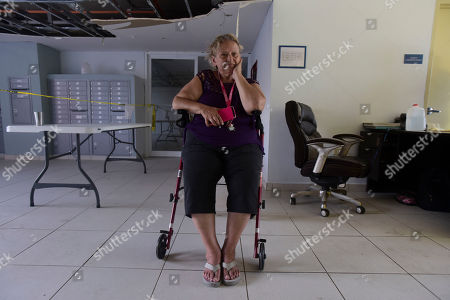 Maria Roman, a resident at the Aires de Manantial home for low-income elderly people, sits in an area where the home's ceiling needs repair in Trujillo Alto, Puerto Rico, . The lights are back on at the residence, but used sparingly, and food has started arriving after Hurricane Maria hit the island on Sept. 20