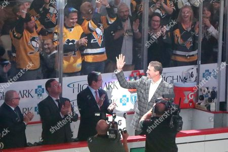 Pittsburgh Penguins Hall-of-Famer, and team owner, Mario Lemieux waves to the crowd as he is introduced during the ceremony to raise the banner for their fifth Stanley Cup Championship before the NHL hockey game against the St. Louis Blues, at PPG Paints Arena in Pittsburgh