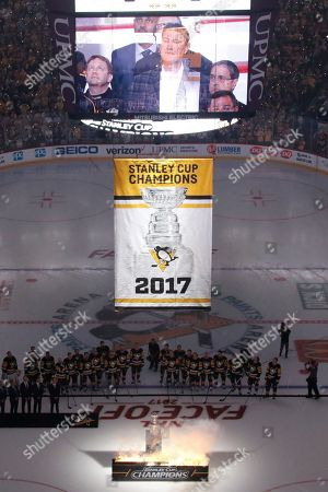 The scoreboard video shows hall-of-famer, and team owner, Mario Lemieux as members of the Pittsburgh Penguins watch the banner for their fifth Stanley Cup Championship is raised before the NHL hockey game against the St. Louis Blues, at PPG Paints Arena in Pittsburgh