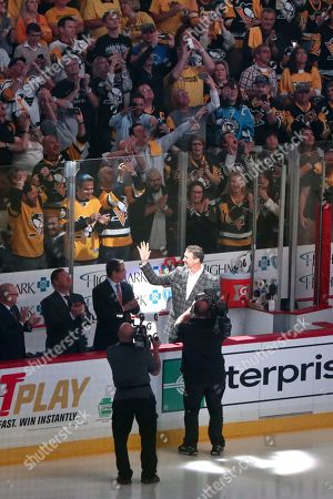 Pittsburgh Penguins Hall-of-Famer and team oener Mario Lemieux waves to the crowd as he is introduced during the ceremony to raise the banner for their fifth Stanley Cup Championship before the NHL hockey game against the St. Louis Blues, at PPG Paints Arena in Pittsburgh