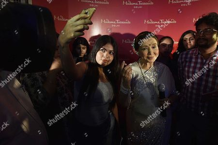 A girl taking selfie with legendary singer Asha Bhosle during an unveiling of her wax figure at the Madame Tussauds museum, on October 3, 2017 in New Delhi, India.