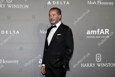 Moncler CEO Remo Ruffini poses for photographers as he arrives for the amfAR charity dinner during the fashion week in Milan, Italy