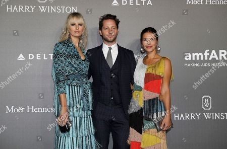 Karolina Kurkova, left, Derek Blasberg, center, and Margherita Missoni pose for photographers as they arrive for the amfAR charity dinner during the fashion week in Milan, Italy
