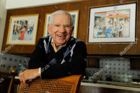 Actor, artist and singer Robert Clary poses near some of his paintings at his home, in Beverly Hills, Calif