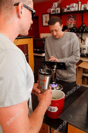 "John Davison receives his ""free fill"" of coffee on the inaugural ""National Fill Your Thermos Brand Bottle Day,"" at Contraband Coffee Bar in San Francisco. This event is being held in select cities and coffee shops throughout the nation, hosted by the iconic Genuine Thermos Brand, to kick off the holiday weekend"
