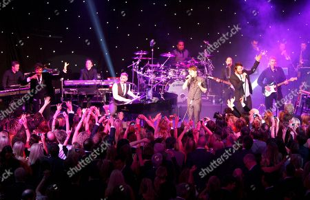From left, Jason Orange, Gary Barlow, Mark Owen and Howard Donald of Take That are seen performing on stage at the 2012 Music Industry Trusts Award ceremony at the Grosvenor House Hotel, in London