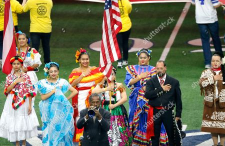 Entertainer Freddie Jones, bottom center, plays the national anthem surrounded by folkloric dancers before an NFL football game between the Los Angeles Rams and Dallas Cowboys, in Arlington, Texas. The League is celebrating Hispanic Heritage Month